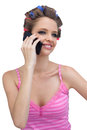 Smiling model with phone wearing hair rollers young on white background Stock Images