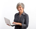 Smiling modern adult woman using laptop in gray collar long sleeves holding while looking at camera isolated on white background Royalty Free Stock Images