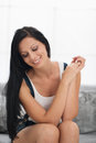 Smiling modern girl black hair sitting couch living room Stock Image