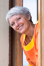 Smiling modern mature woman with grey hairs looking from the window Royalty Free Stock Image