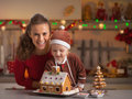 Smiling mother and baby decorating christmas cookie house in kitchen Royalty Free Stock Photo