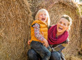 Smiling mother and child near haystack portrait of Royalty Free Stock Photography