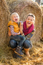 Smiling mother and child near haystack portrait of Stock Images