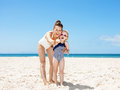 Smiling mother and child pointing in camera at sandy beach Royalty Free Stock Photo