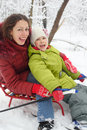 Smiling mother, daughter pose on sled Stock Images