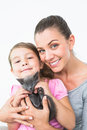 Smiling mother and daughter sitting with pet kitten together Royalty Free Stock Photo