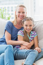 Smiling mother and daughter sitting together on sofa at home portrait of Royalty Free Stock Photography