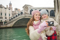 Smiling mother and daughter taking photos near ponte di rialto modern family a winter break to enjoy inspirational adventure in Royalty Free Stock Photo