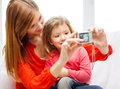 Smiling mother and daughter taking picture family children technology happy people concept with digital camera Stock Images