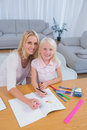 Smiling mother drawing with her little girl in the living room Royalty Free Stock Photos