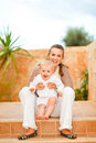 Smiling mother and happy baby sitting on staircase Stock Photos