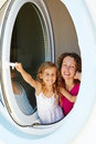 Smiling mother and her daughter look out from window little made as porthole Royalty Free Stock Photo