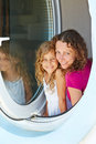 Smiling mother and her daughter look out from window little made in form of porthole Stock Image