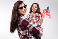 Smiling mother holding her daughter and posing in the studio Royalty Free Stock Photo