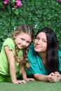 Smiling mother and little daughter lie on lawn in garden next to verdant fence Stock Image