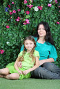 Smiling mother and little daughter sit on grass in garden next to verdant fence Royalty Free Stock Image