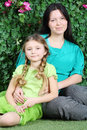 Smiling mother and little daughter sit on lawn in garden next to verdant fence Royalty Free Stock Images