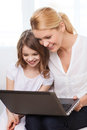 Smiling mother and little girl with laptop at home family child technology concept Stock Photography