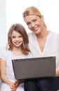 Smiling mother and little girl with laptop at home family child technology concept Royalty Free Stock Image