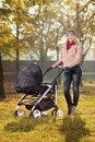 A smiling mother posing with a baby stroller Royalty Free Stock Image