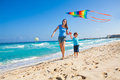 Smiling mother and son holding arms with kite happy flying in the sky during sunny day on beach coast ocean waves Royalty Free Stock Photo