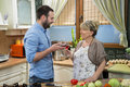 Smiling mother and son toasting with wine in the kitchen happy her adult talking to each other while red preparing food Stock Image