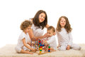 Smiling mother with three kids playing home wooden toy Stock Photography