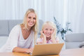 Smiling mother using laptop with her daughter in the living room Royalty Free Stock Images