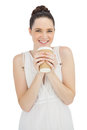 Smiling natural model in white dress drinking coffee while posing on background Stock Photo