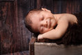 Smiling newborn baby boy sleeping in a rustic crate day old on his stomach vintage weathered wooden shot the studio on barn Stock Photos