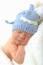 Smiling newborn baby in shark hat on fluffy white blanket Stock Photos
