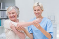 Smiling nurse assisting senior patient in raising arm portrait of female at clinic Royalty Free Stock Photo