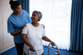 Smiling nurse assisting senior woman in walking with walker Royalty Free Stock Photo