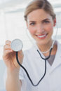 Smiling nurse showing her stethoscope Royalty Free Stock Photo