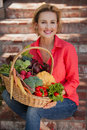 Smiling nutritionist holding basket full of vegetables outdoors. Healthy lifestyle.
