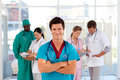 Smiling octor with his team in the background Royalty Free Stock Photo