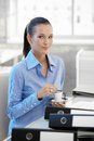 Smiling office girl having coffee worker sitting at desk looking at camera Stock Photos