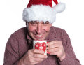 Smiling old casual man wearing a santa hat is drinking a hot te tea on white background Royalty Free Stock Photography
