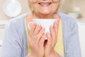 Smiling old woman holding cup of tea five o clock close up sitting in kitchen and Royalty Free Stock Images