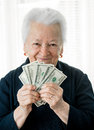 Smiling old woman holding money in hands