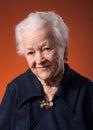 Smiling old woman orange background Royalty Free Stock Photos
