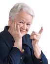 Smiling old woman pointing upwards on white background Stock Images