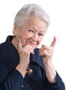 Smiling old woman pointing upwards on white background Stock Image
