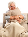 Smiling old woman resting at home with pillow in hands and blanket on feet isolated on white background Stock Image