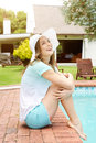 Smiling older woman relaxing by pool Royalty Free Stock Photo