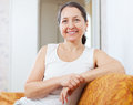 Smiling ordinary mature woman in home interior Royalty Free Stock Image
