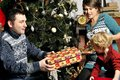 Smiling parents giving christmas present to son at home in Stock Photography