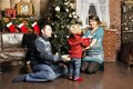 Smiling parents giving christmas present to son at home Stock Images