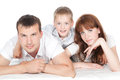 Smiling parents with little son lying on white Royalty Free Stock Photography
