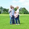 Smiling parents with their kids in the park happy family of four standing together Royalty Free Stock Image